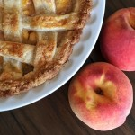 Peach Pie alongside fresh peaches